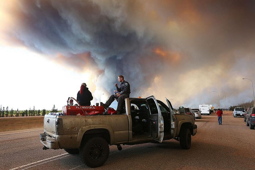 A group trying to rescue animals from Fort McMurray waiting at a road block as smoke rises from a fire. Officials say the out-of-control inferno may keep burning for months without significant rainfall.