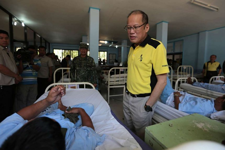 In this handout photo taken on April 13 and released by Malacanang Photo Bureau, Philippine President Benigno Aquino (right) talking to one of the wounded soldiers who clashed with Abu Sayyaf Islamic militants.
