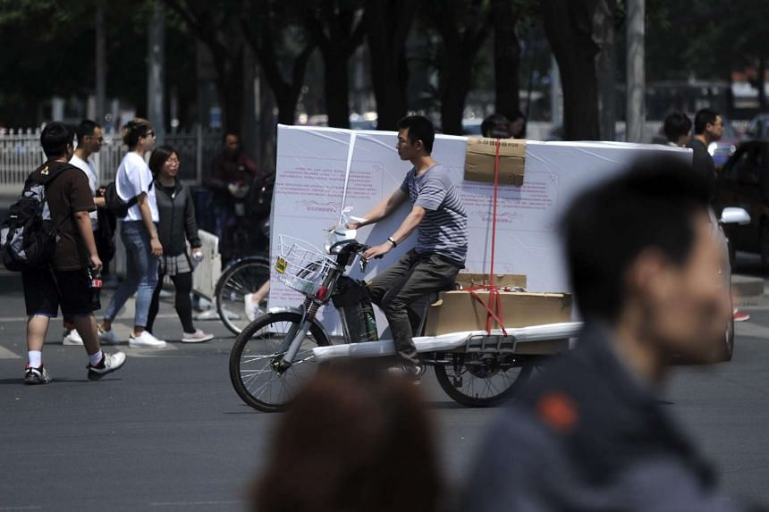 A man riding an electric bicycle with goods along a street in Beijing on May 8, 2016.