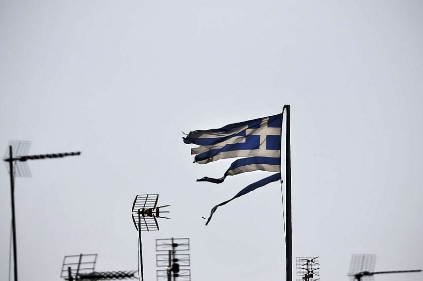A frayed Greek national flag flutters among antennas atop a building in central Athens, Greece in this file photo taken July 20, 2015.