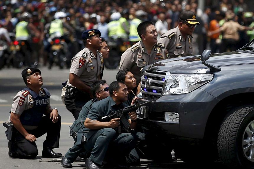 Police officers react near the site of an attack in Jakarta, Indonesia, in this Jan 14, 2016 file photo.