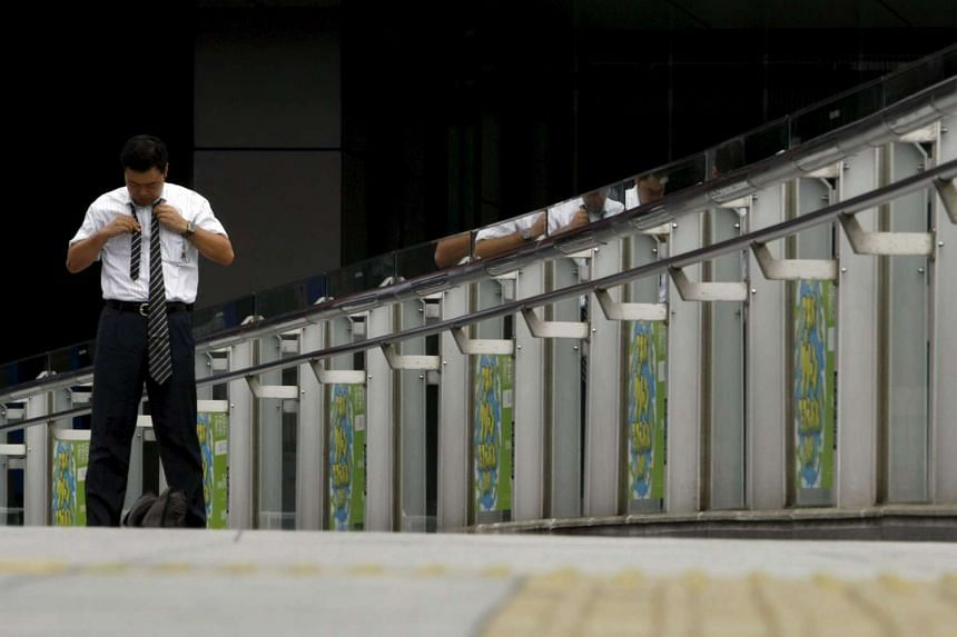 A man ties his necktie on a street in Tokyo. Japanese price-adjusted real wages in March 2016 rose the most in 5-1/2 years due to stalling inflation and rising nominal wages.