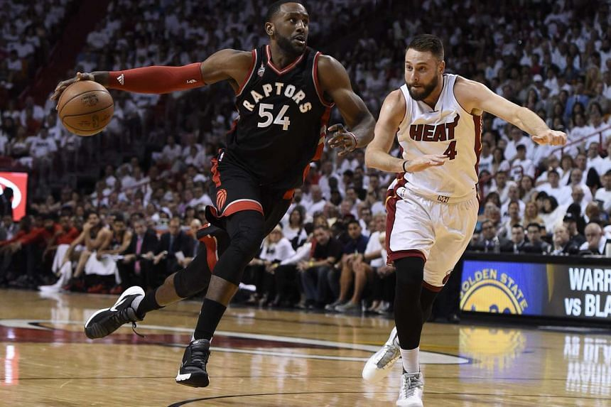 Toronto Raptors forward Patrick Patterson (left) drives the ball past Miami Heat forward Josh McRoberts (right) during the second half of game three of the NBA Eastern Conference semifinals basketball game between the Toronto Raptors and the Miami He