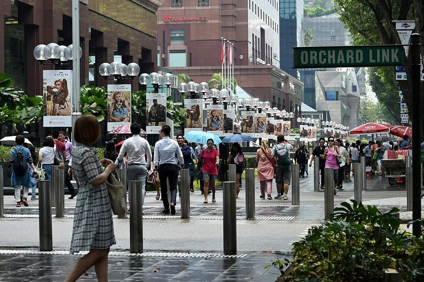 Pedestrians walk along the Orchard Road shopping district. Retailers are experiencing a significant tightening of their cash flow positions as creditors take steps to protect themselves against possible defaults.