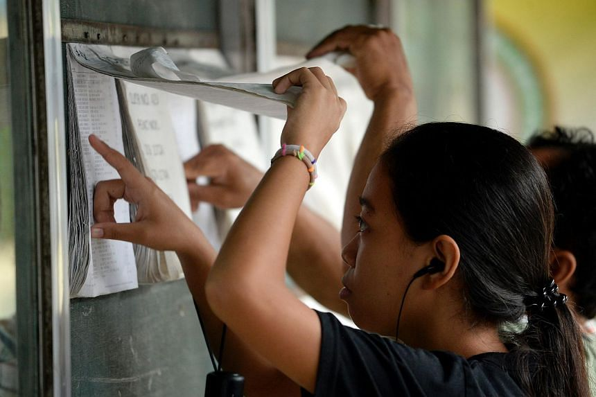 A woman looks for her name and assigned precinct at the Daniel Aguinaldo National High School in Davao City, on the southern island of Mindanao on May 8, 2016, ahead of the presidential and vice presidential elections.