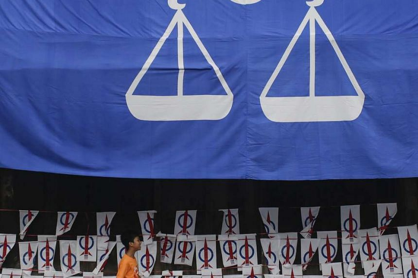 A young boy passing by the Barisan National Party flag and Democratic Action Party posters at Kuching, Sarawak, on May 6, 2016.