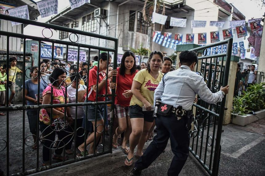 A security guard (right) opening the gate for voters to enter during the elections at a polling centre in Manila, on May 9, 2016.