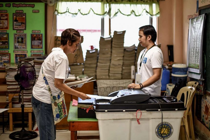 An elderly Filipino woman (left) placing her ballot paper into a vote counting machine during the elections at a polling centre in Manila on May 9, 2016.