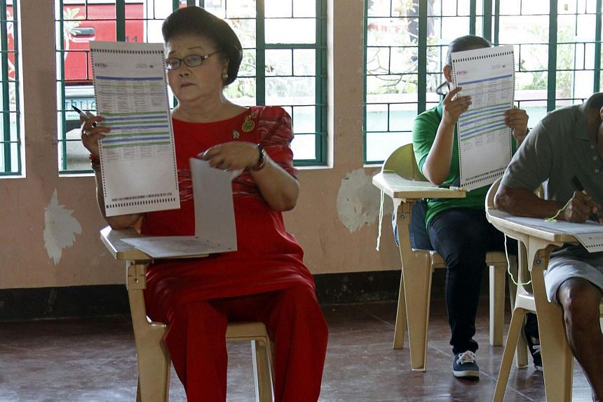 Former Philippine first lady Imelda Marcos (left) casting her vote at a polling station in Batac, Ilocos norte province, north of Manila, on May 9, 2016.