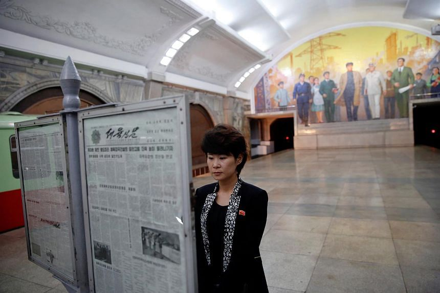 A woman reading newspapers displayed inside a subway station visited by foreign reporters on a government organised tour in central Pyongyang, North Korea, on May 7, 2016.