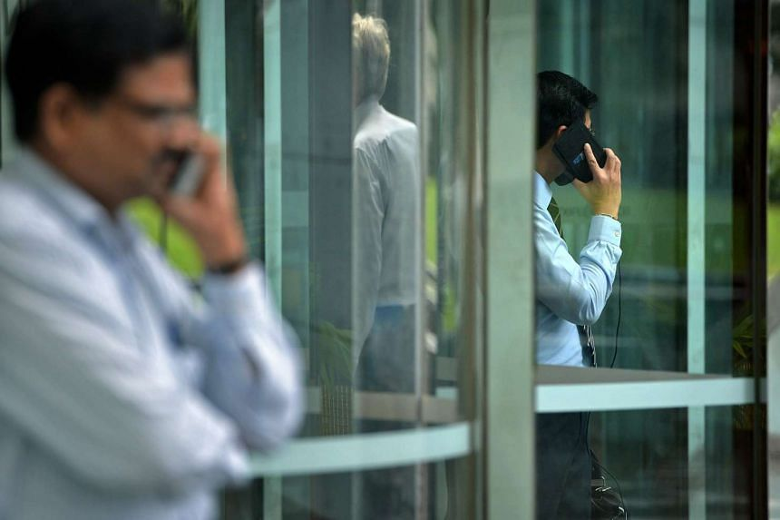 Office workers chatting on their phones during lunch hour in the Central Business District at Raffles Place, on Feb 23, 2016.