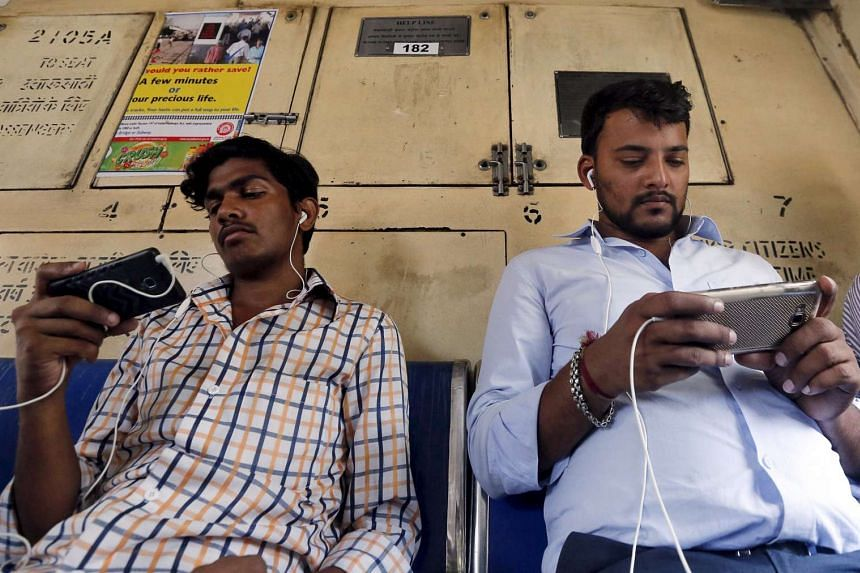 Commuters watch videos on their mobile phones as they travel in a suburban train in Mumbai, India, on April 2, 2016.