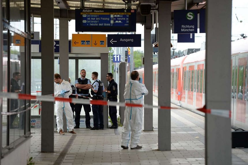 German forensic investigators and uniformed police officers next to a local train at the railway station in Grafing, near Munich, on May 10, 2016.