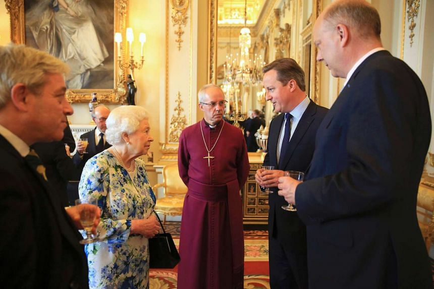 Britain's Queen Elizabeth II speaks with British Prime Minister David Cameron (second from right) during a reception in Buckingham Palace, on May 10, 2016.