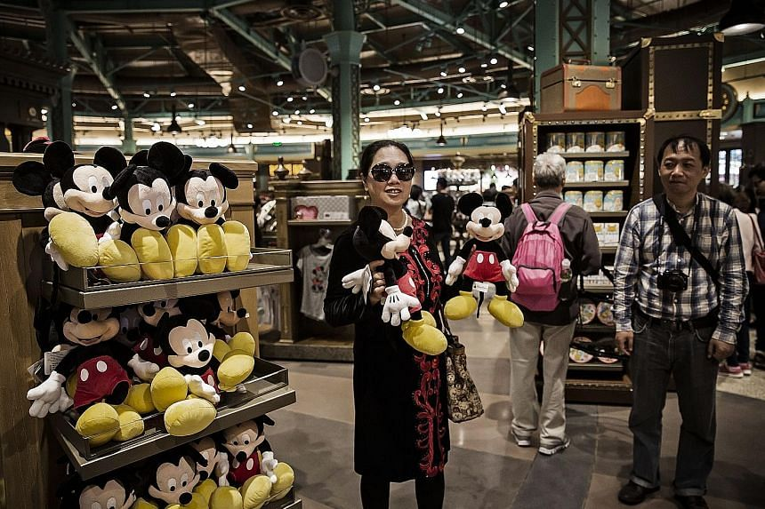 The resort's many visitors walking past a gate and (above) a customer checking out the Mickey Mouse merchandise inside a World of Disney store.