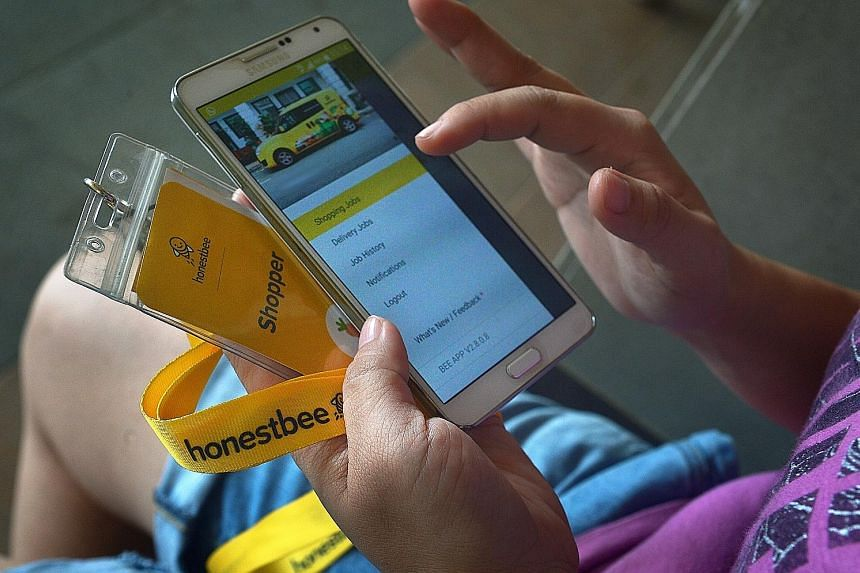 An honestbee shopper checking an app through which shoppers receive orders they have to fill at supermarkets. The firm's CEO and co-founder Joel Sng said shoppers' pay fluctuates based on customer demand.