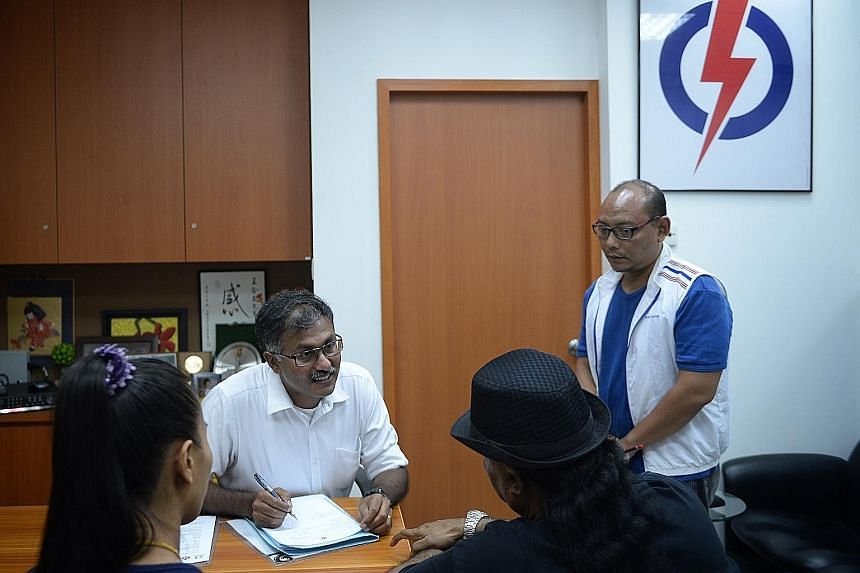 (Above) Mr Murali speaking with a resident during his first Meet-the-People Session at the Bukit Batok PAP branch office last night. (Left) He was sworn in as MP for the constituency at Parliament House earlier in the day.