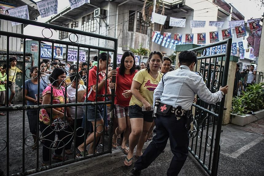 Voters entering a polling centre in Manila yesterday. Analysts said that with Mr Duterte poised to become the next president of the Philippines, it may be time for the nation to move beyond the elections.