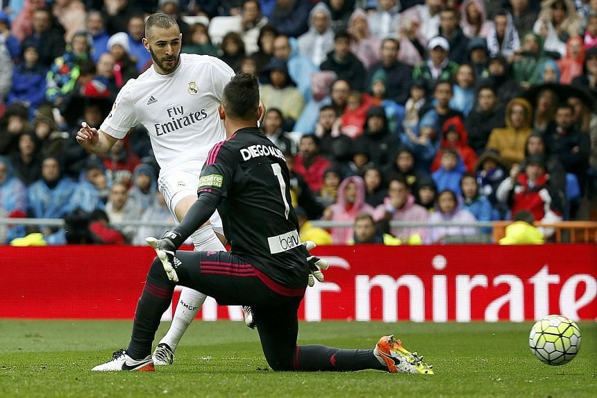 Real Madrid striker Karim Benzema scores their second goal against Valencia on Sunday. Real won the La Liga clash 3-2 to set up a chance to overtake league leaders Barcelona on the final day of the league competition next Saturday.