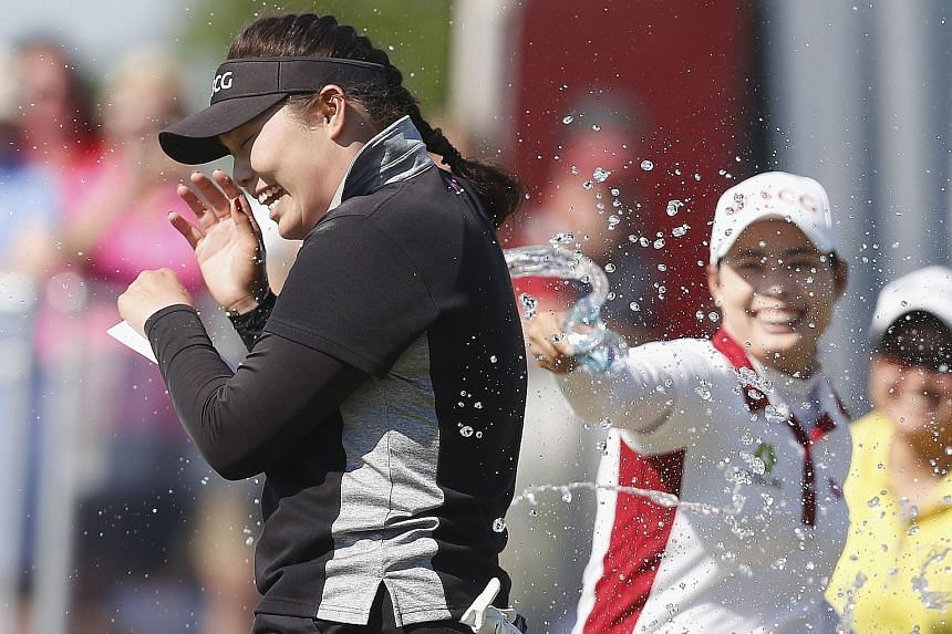 Ariya Jutanugarn being sprayed with champagne as she celebrates winning the Yokohama Tire Classic with her sister, Moriya. The Thai golfer had needed a par putt in her final hole to confirm her victory.