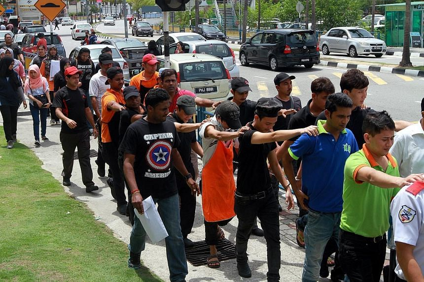 Foreign workers in Malaysia without valid travel documents or work permits being led away by enforcement officers during an Immigration Department raid at a mall in Penang this month. There are some two million illegal foreign workers in the country.
