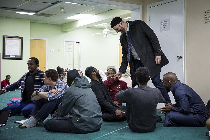 Mr Webb greets attendees of a seminar at the Islamic Research and Humanitarian Service Centre of America. He has held live monthly video chats to refute the religious claims of ISIS.