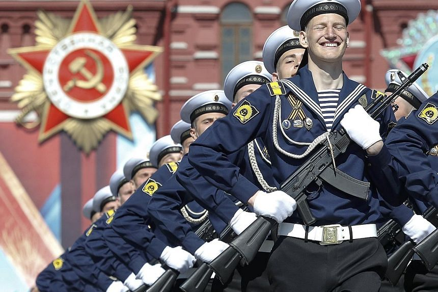 Russian servicemen marching during the Victory Day parade, marking the 71st anniversary of the victory over Nazi Germany in World War II, in Moscow's Red Square yesterday. President Vladimir Putin, alongside several Soviet war veterans, attended the