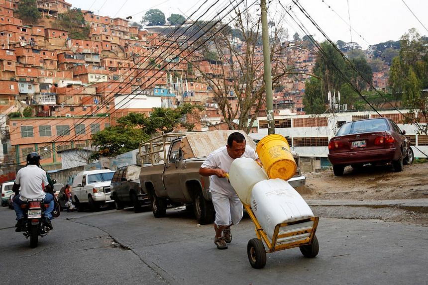 """A man pushing a wheelbarrow loaded with water containers in a neighbourhood called """"The Tank"""" at the slum of Petare in Caracas, Venezuela, on March 17, 2016."""