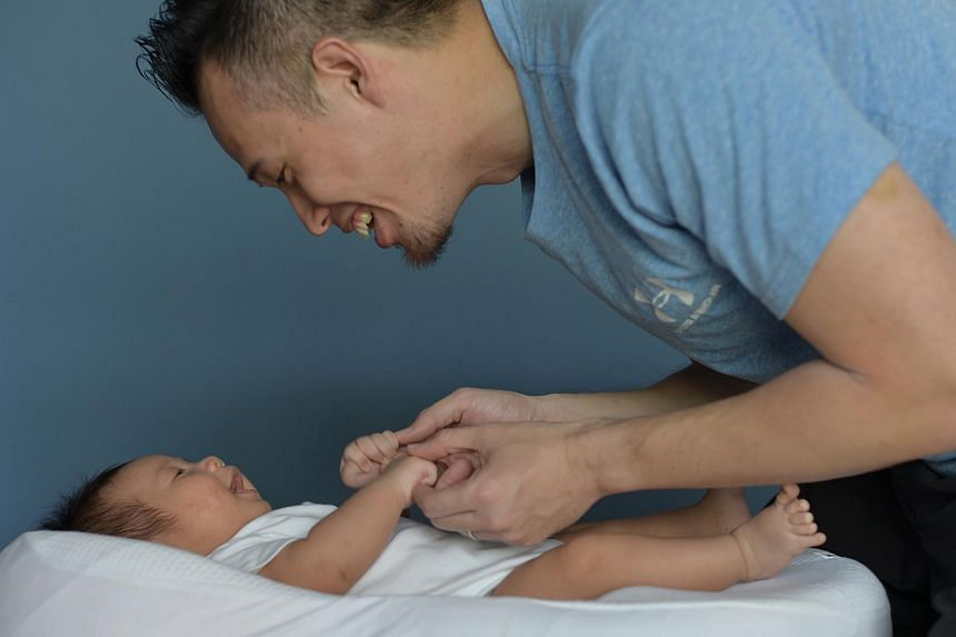 Posed photo of a father with his two-month old son.