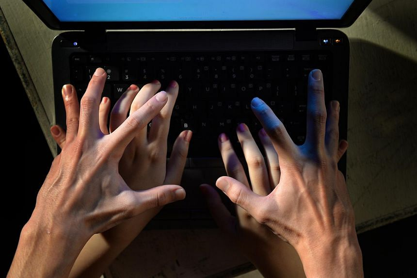 Posed photograph of hands over a laptop to illustrate an article on sexual crime.