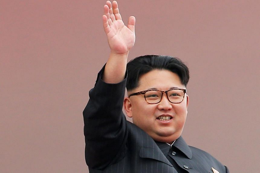 North Korean leader Kim Jong Un waving to the crowd as he presides over a mass rally and parade in Pyongyang.