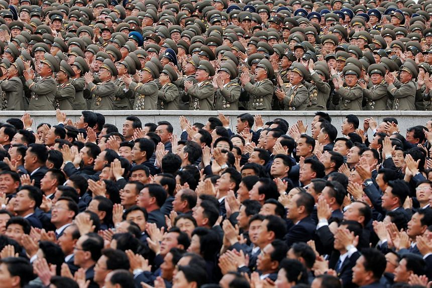 Party and military officials reacting as North Korean leader Kim Jong Un appears at the mass rally and parade.