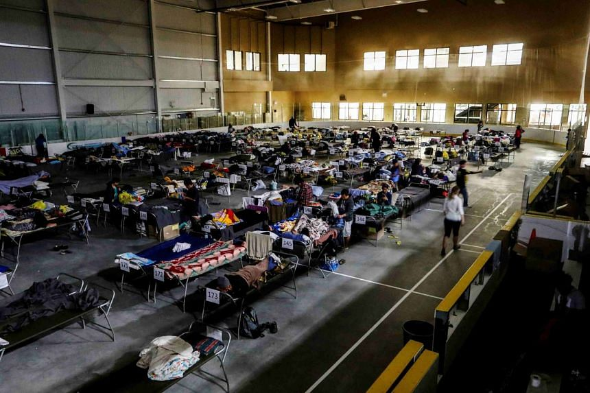 Evacuees from the Fort McMurray wildfires use a hockey rink full of beds  in Lac la Biche, Alberta in Canada.