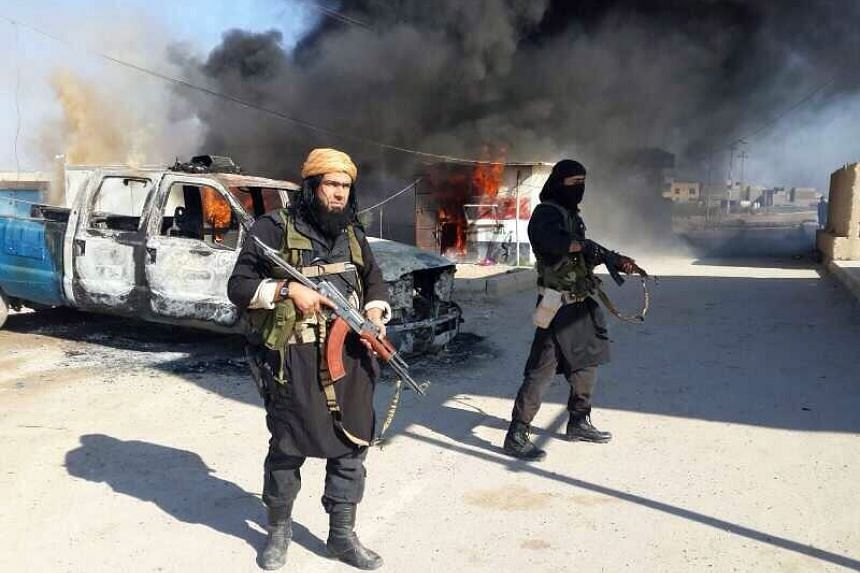 An image uploaded to an Islamic website on Jan 8, 2014, allegedly showing Shakir Wahib (left), and Abu Wahib standing next to burning cars in Iraq.