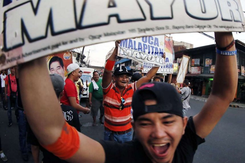 Filipino voters celebrate in a street after the news of a partial count result, in Calookan city, north of Manila.