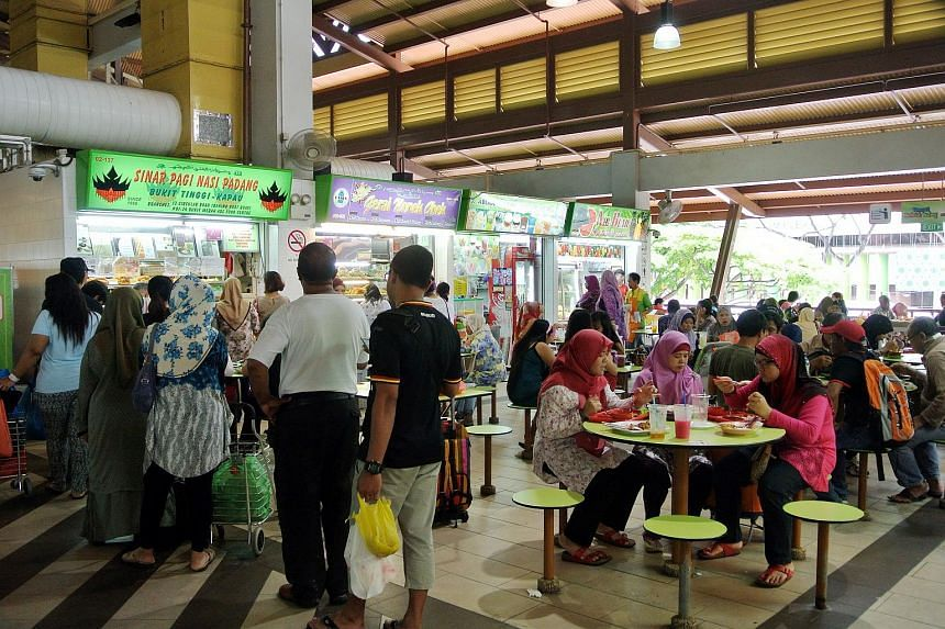 People queuing to buy food while others are having their meals at the Geylang Serai Hawker Centre.