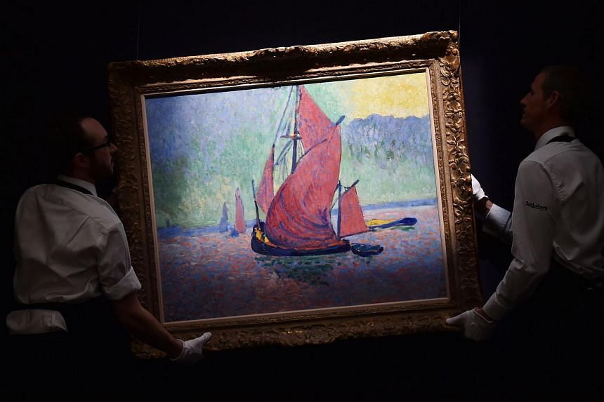 Members of staff pose with artwork entitled 'Les Voiles Rouges' 1906, by French artist Andre Derain, during a press preview of Sotheby's forthcoming Impressionist, Modern and Contemporary Art Sale in New York, at Sotheby's in London, on Apr 8, 2016.