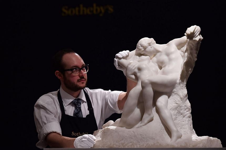A member of staff poses with artwork entitled 'L'Eternal Printemps' 1901-02, by French artist Auguste Rodin, during a press preview of Sotheby's forthcoming Impressionist, Modern and Contemporary Art Sale in New York, at Sotheby's in London, on Apr 8