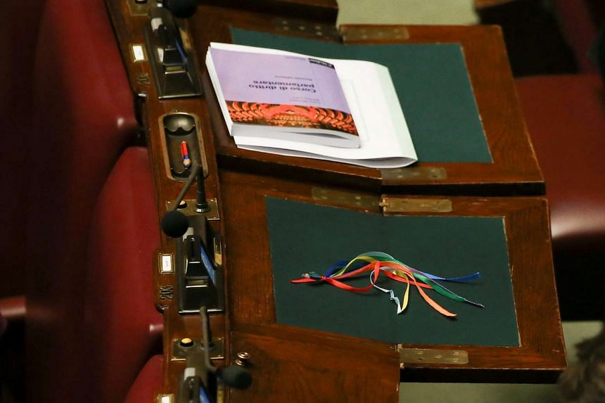 Colored ribbons are seen on a desk before the final vote on gay and unmarried civil unions at the Italy's lower house of Parliament in Rome, Italy on May 11, 2016.