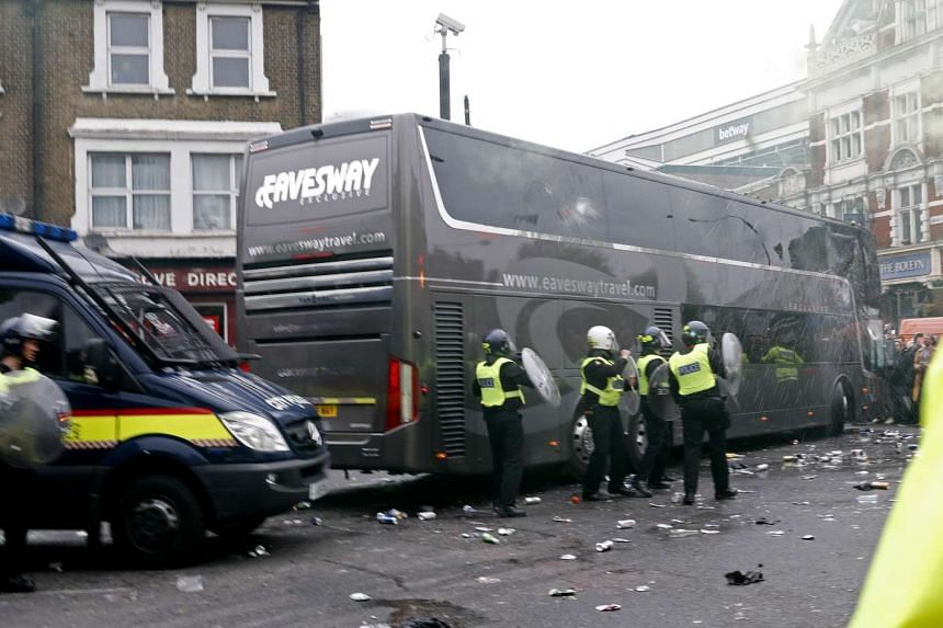 West Ham fans attack Manchester United's team bus before the football match between West Ham United and Manchester United in east London on May 10, 2016.