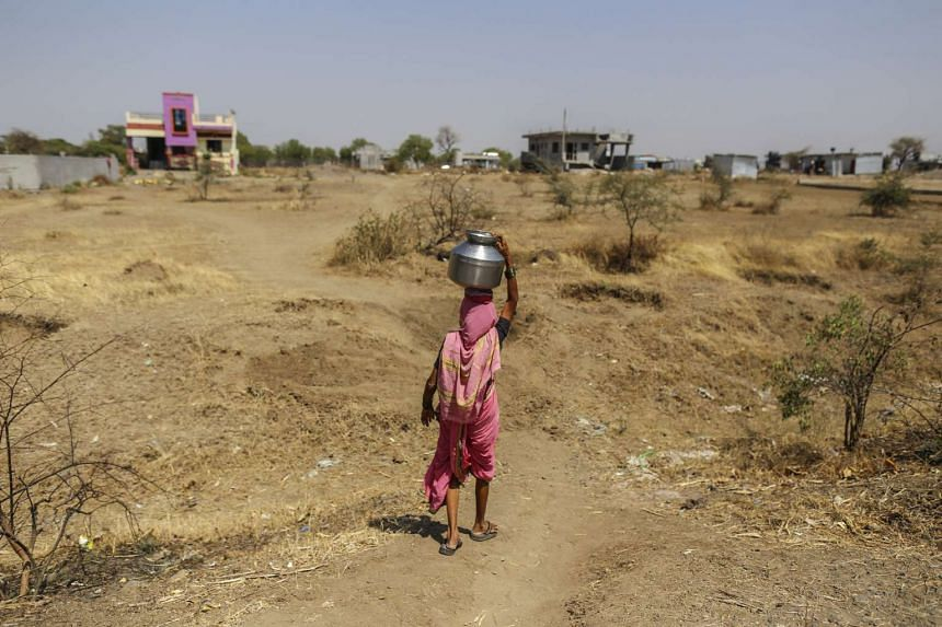A woman carries a water container on her head filled from public drums at a village in Beed district, Maharashtra, India, on April 15, 2016.