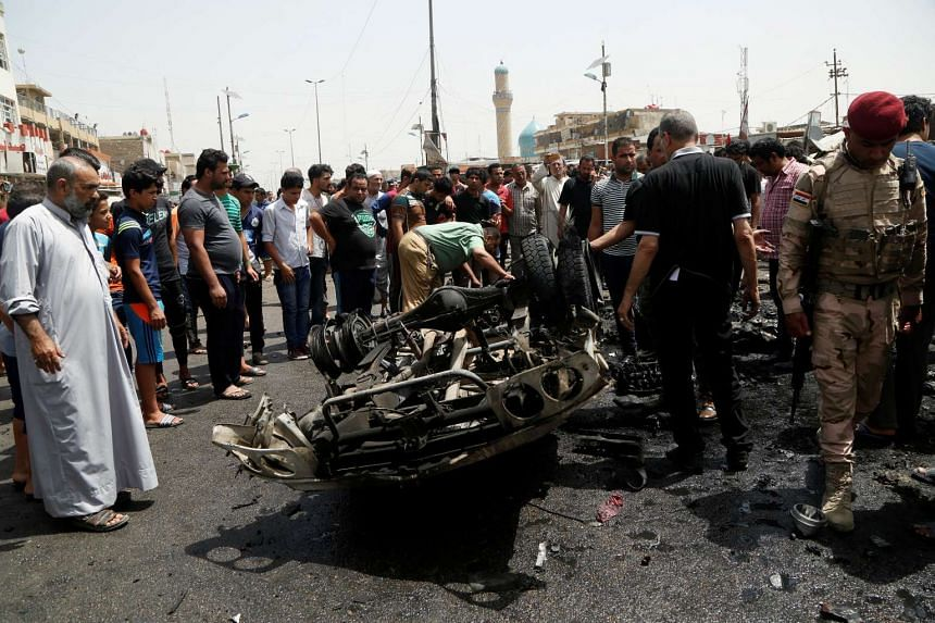 People gather at the scene of a car bomb attack in Baghdad's mainly Shi'ite district of Sadr City, Iraq on May 11, 2016.