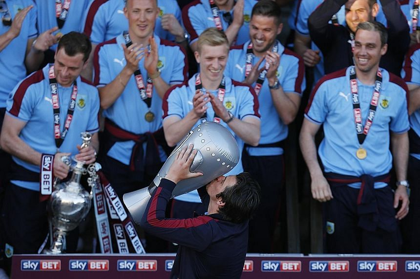 Burnley's Joey Barton pointedly celebrates with a blow-up trophy on Monday, after a shortfall of two Championship winners' medals meant that he and James Tarkowski missed out. The club apologised for the error and the players were finally given their