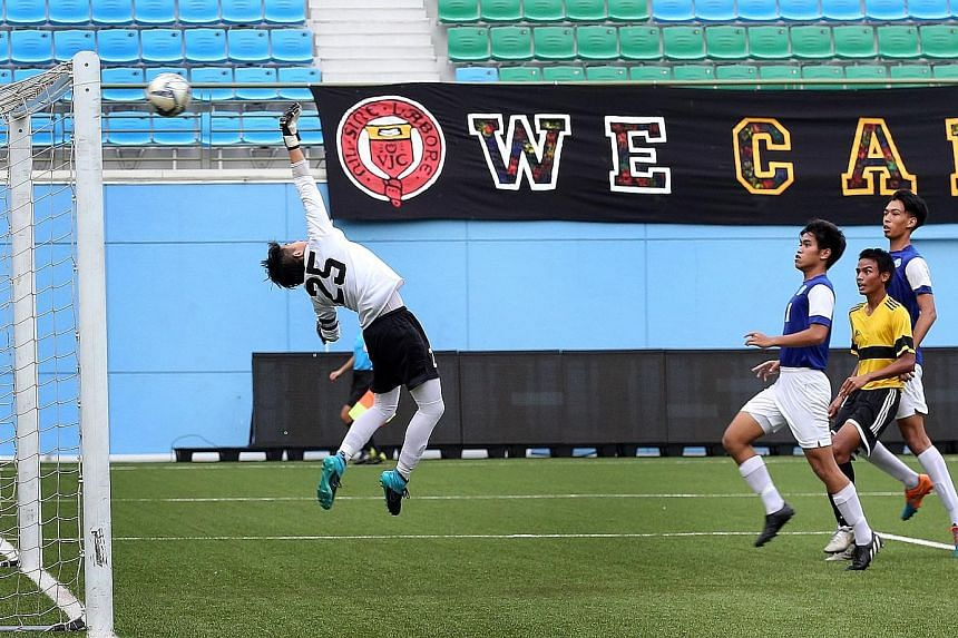 Meridian Junior College (MJC) goalkeeper Dagan Lim (left) tipping a goal-bound shot over the bar, as his team secured a 1-0 win over Victoria Junior College in the Schools National A Division boys' football final at the Jalan Besar Stadium yesterday.