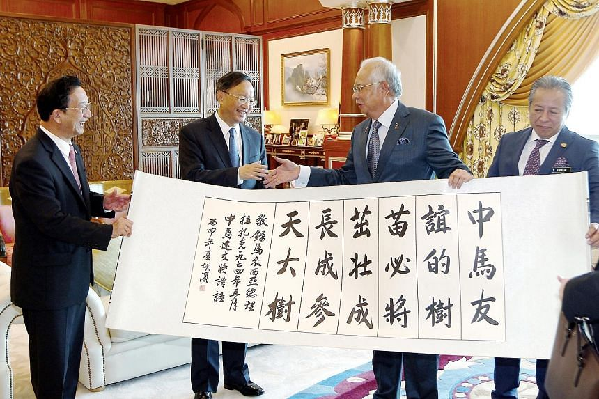 Malaysian Prime Minister Najib Razak and China's State Councillor Yang Jiechi shaking hands after the presentation of a calligraphy scroll to the Malaysian leader yesterday. Also present at the event were Malaysian Foreign Minister Anifah Aman (right