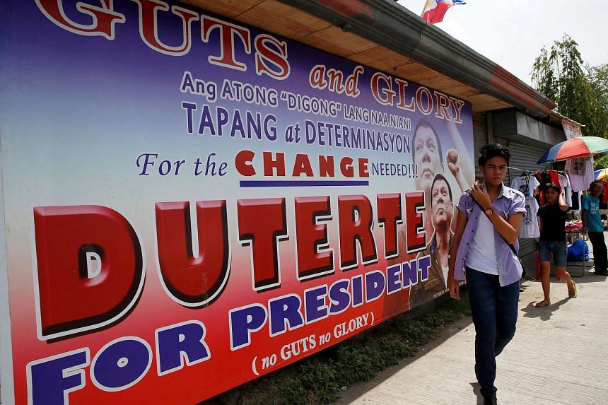 Residents walking past an election campaign poster of leading presidential candidate Rodrigo in Davao city, southern Philippines, on May 11, 2016.