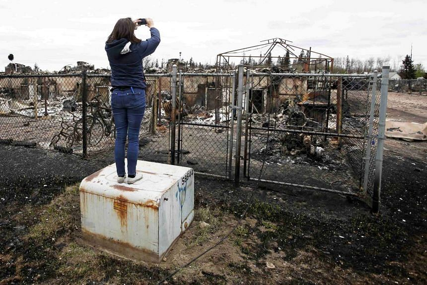 A woman takes photos of the burned remains of a house.