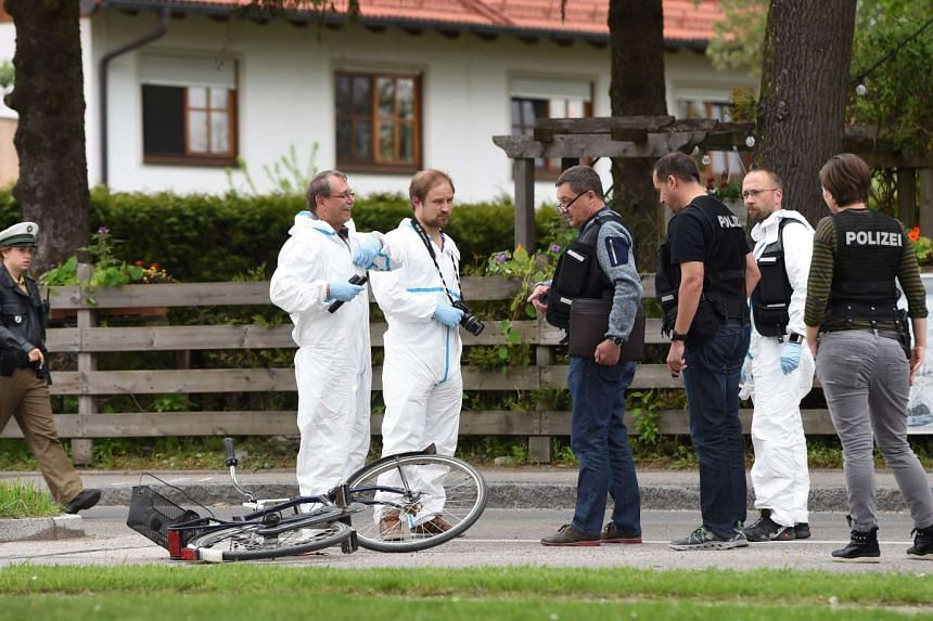 Forensic experts and policemen working near a train station in Grafing, near Munich, where a man killed one person and wounded three others in a knife attack on May 10, 2016.