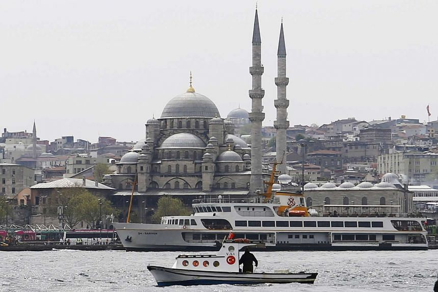 A fishing boat sails in the Golden Horn with 17th-century Ottoman era New Mosque (Yeni Cami) in background in Istanbul, Turkey, on April 14, 2016.