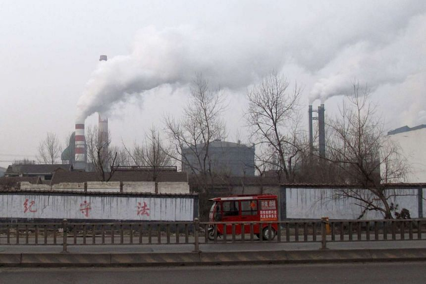 A motorcyclist rides past a steel firm in Linyi, Shandong province, China, on Feb 22, 2016.